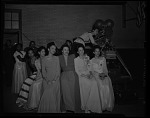 [Unidentified group of women in formal dress sitting with a woman filming behind them] [cellulose acetate photonegative]