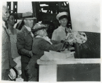 Mrs. Edith Savoy Morgan, daughter of the late Edward A. Savoy, christens the Liberty ship SS Edward A. Savoy by breaking a bottle of champagne against its hull while others look on, Bethlehem-Fairfield Shipyard
