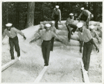 Three African American sailors walking across and trying to balance on wooden beams that are laid across a sand pit while others look on and wait their turn at U.S. Navy Receiving Station, Camp Robert Smalls