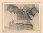 Photograph of an African American vocational instructor showing two students how to operate a drill press, Sylvania, Georgia, 1951