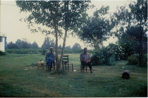 Charlie Hill and unidentified man (r. to l.), seated on a lawn
