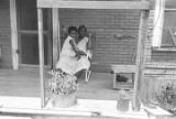 Woman and little girl sitting together in a chair on the front porch of a house in Newtown, a neighborhood in Montgomery, Alabama.