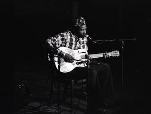 Taj Mahal in concert at Northfield, Mass.: Taj Mahal seated, playing steel guitar