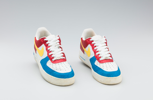 Red, white, yellow, and blue Nike sneakers worn by Big Boi of Outkast