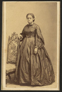 [Full-length portrait of an unidentified African American woman, standing beside a chair]
