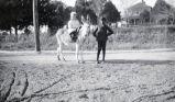 White girl on mule, African-American boy standing beside