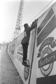 Young boy climbing the wall surrounding Hartwell Field, Mobile, Alabama.