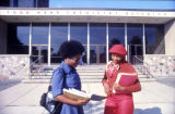 Two students discuss their homework in front of the Wehr Chemistry Building
