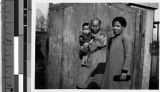 Family standing in front of a wooden gate, Fushun, China, 1939