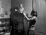 [Woman playing trumpet : black-and-white photonegative]
