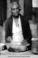 Elderly African American woman, wearing white dress, dark sweater, and cameo brooch, standing over a mixing bowl.