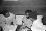 Robert Flowers and Barbara Howard Flowers seated with another man at a table at the Laicos Club in Montgomery, Alabama.