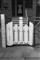 Jasper Wood Collection: Front gate and woman standing on porch with hands on hips