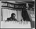 [Vernon Jordan listens as Ossie Davis speaks from a podium at a National Urban League conference in Detroit, Michigan]