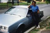 Mari Evans posing beside a car