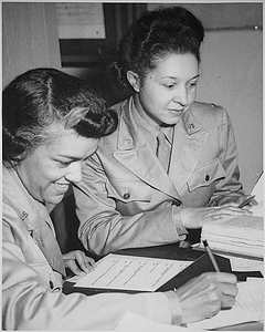 """""""WAACs at work in Temp. Bldg. `M', 26th Street, Washington, DC, WAAC Headquarters. Left to right: Lts. Harriet West and Irma Cayton,...going over their recruiting schedule report."""""""