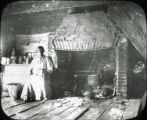 African American woman sitting next to fireplace in rural kitchen, Eastern Shore, Maryland and/or Virginia