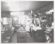Mississippi State Sovereignty Commission photograph of the interior of Stanley's Cafe showing a waitress and men eating while seated at tables, booths and counter, Winona, Mississippi, 1961 November 1