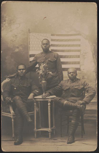 [Three unidentified African American soldiers in uniforms with vase of flowers in front of American flag and painted backdrop]