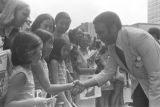 "Andrew Young shaking hands with a little girl in a crowd in downtown Atlanta, Georgia, during the Democratic National Committee's regional conference, ""Victory '68."""