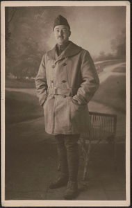 [Unidentified African American soldier in uniform, overcoat, and overseas cap in front of painted backdrop]