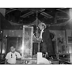 "William Woogie"" Harris playing mirrored piano and singing into microphone on stage above bar at Crawford Grill No. 2, with bartender Tom West in background"""