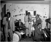 Five-man African-American band (piano, trumpet, drums, saxophone and singer), on stage at the Elks Club, Atlanta, Georgia, December 16, 1955. Segregated Christmas party sponsored by Davison-Paxon Company for its African-American employees