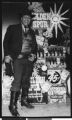 African American man dressed in Old West costume, standing in front of display of Golden Spur, Los Angeles, ca. 1951-1960