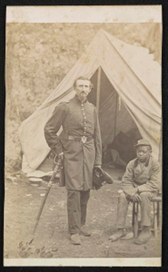 [Major Luzerne Todd of Co. D, 23rd New York Infantry Regiment and Co. B, 86th New York Infantry Regiment in uniform with sword and unidentified young African American servant in front of tent]