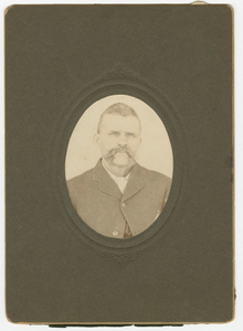 Photograph of a man with a mustache wearing a dark jacket
