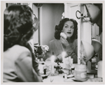 Portrait of actress Hilda Simms in a dressing room applying makeup before a performance, ca. 1940s