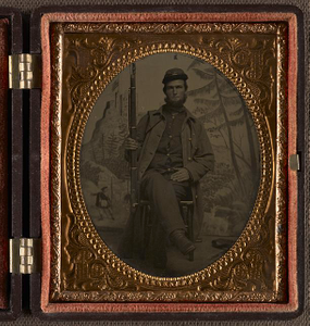 [Unidentified soldier in Union uniform with rifle in front of painted backdrop showing structure on mountain and man in historical dress]