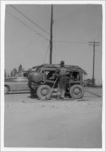 Photograph of African-American man with a piece of road construction equipment, Manchester, Georgia