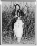 [Zora Hurston, full-length portrait, standing, facing front, beating tall drum]