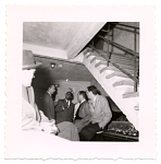 [Flip Phillips (second from left), Norman Granz (second from right), and other men,talking under staircase, undated.] [Black-and- white photoprint]