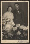 [Wedding portrait of a World War II Corporal with his new bride, flowers in the foreground]