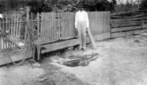 Unidentified man standing near a trough.
