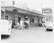 Mississippi State Sovereignty Commission photograph of four males standing outside of Stanley's Cafe and the Trailways Bus Depot, Winona, Mississippi, 1961 November 1