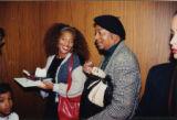 Terry McMillan eating cake with Eugene Redmond