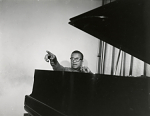 [Billy Strayhorn, seated at piano, pointing : black-and-white photoprint.]