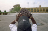 Boy Holding Catcher's Mitt Outside Stadium