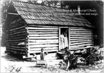 [Photograph of an African American family in front of their log cabin house in or near Richmond County, Georgia, late 19th century]