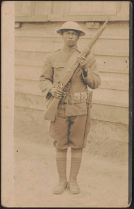[Unidentified African American soldier in uniform and helmet with rifle and knife hanging from cartridge belt]