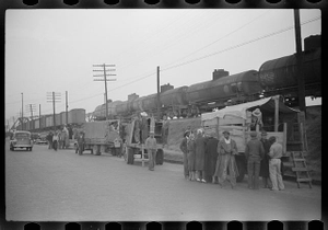 Day laborers being hired for cotton picking on Mississippi and Arkansas plantations. Between four and six-thirty every morning during the season, near the Hallan Bridge in Memphis, Tennessee, crowds of Negroes in the streets gather and are loaded into trucks by drivers who bid, and offer them anywhere from fifty cents to one dollar per day