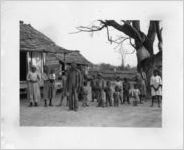 African American family and children standing in front of their homes