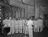 """African American servicemen singing on stage during a recording of the """"Sgt. Gene Autry"""" radio program at the municipal auditorium in Birmingham, Alabama."""