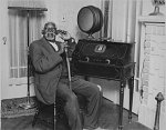 [Elderly African American man sitting in front of a radio, black-and-white photoprint.]