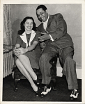 [Beatrice Ellis; AKA Evie Ellington sitting in a chair with Duke Ellington sitting on the arm of the chair : black-and-white photoprint.]