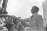 "Andrew Young shaking hands with a young man in a crowd in downtown Atlanta, Georgia, during the Democratic National Committee's regional conference, ""Victory '68."""