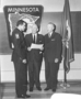 Gene A. Shokency, the first African American to receive an appointment with the State Highway Patrol, with Governor Rolvaag and Commissioner Marshall
